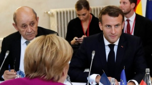 French Foreign Minister Jean-Yves Le Drian, left, German Chancellor Angela Merkel, center, and French President Emmanuel Macron meet during a joint Franco-German cabinet meeting in the government building of Toulouse, southwestern France, Wednesday, Oct.16, 2019. (Guillaume Horcajuelo/Pool Photo via AP)