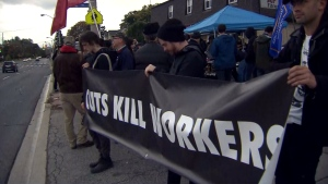 Protesters gather outside Ontario Premier Doug Ford's constituency office in Etobicoke to demand action on preventing workplace deaths in the province.