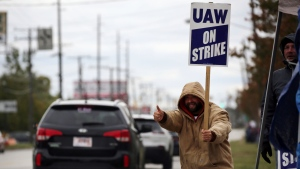 A member of UAW Local 1005 gives a thumbs up to drivers outside GM Parma plant on Brookpark Road on Wednesday, Oct. 16, 2019, in Parma, Ohio. (Gus Chan/The Plain Dealer via AP)