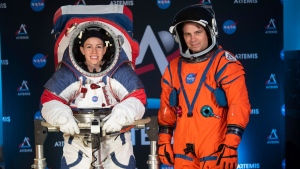The two NASA spacesuit prototypes for lunar exploration, one for launch and re-entry aboard the agency's Orion spacecraft, known as the Orion Crew Survival Suit, is worn by Dustin Gohmert, right, and one for exploring the surface of the Moon's South Pole, known as the Exploration Extravehicular Mobility Unit (xEMU) is worn by Kristine Dans on Tuesday, Oct. 15, 2019, at NASA Headquarters in Washington. (AP / Kevin Wolf)