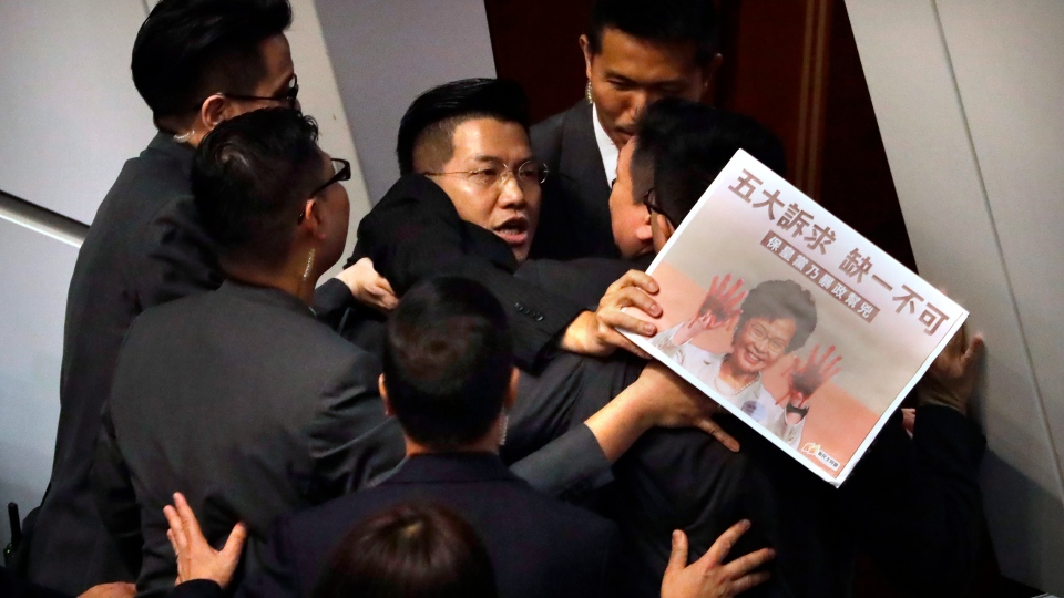 Pro-democracy lawmaker Gary Fan, center, is forcibly removed by security officials as he protests while Hong Kong Chief Executive Carrie Lam delivers her speech at a question and answer session at the Legislative Council in Hong Kong, Thursday, Oct. 17, 2019. (AP Photo/Mark Schiefelbein)