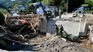 Japan's Self-Defense Forces' members work to remove piled driftwood at a bridge after Typhoon Hagibis hits the town in Marumori, Miyagi prefecture, northern Japan Wednesday, Oct. 16, 2019. (Kyodo News via AP)
