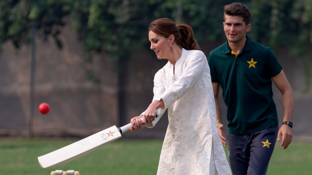 Kate, Duchess of Cambridge plays cricket as Pakistani bowler Shaheen Afridi looks on, during her visit at the Pakistan Cricket Academy in Lahore, Pakistan, Thursday, Oct. 17, 2019. (AP Photo/B.K. Bangash)