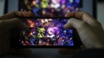 "The game ""Hearthstone"" is seen on a smartphone in this 2018 photo. Video game company Activision Blizzard suspended three American University esports players for six months after they held up a ""Free Hong Kong, boycott Blizz"" sign during their championship match last week. (CNN via Metin Aktas/Anadolu Agency/Getty Images)"