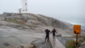 Visitors to the lighthouse in Peggy's Cove, N.S. brave the elements as a major storm lashes the region on Thursday, Oct. 17, 2019. The slow-moving low pressure system features strong gusts and localized downpours causing delays in transportation and power outages across the Maritimes. THE CANADIAN PRESS/Andrew Vaughan