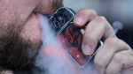 FILE - In this Friday, Oct. 4, 2019 photo, a man using an electronic cigarette exhales in Mayfield Heights, Ohio. (AP Photo/Tony Dejak)
