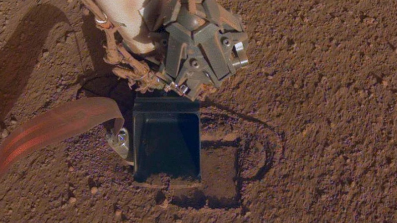 This October 2019 photo made available by NASA shows InSight's heat probe digging into the surface of Mars. (NASA/JPL-Caltech via AP)