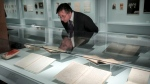 Declan Kiely, director of special collections and exhibitions at the New York Public Library, review manuscripts during the installation of the library's J.D. Salinger exhibit, Wednesday, Oct. 16, 2019, in New York. (AP Photo/Bebeto Matthews)