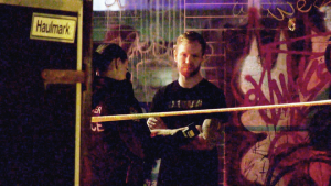 CTV News cameras captured a Vancouver police officer with a breathalyzer in hand interviewing a man who appears to be the band's bassist, Robbie Swartwood, behind police tape, as dozens of other officers closed several blocks of East Hastings Street to investigate. (CTV)