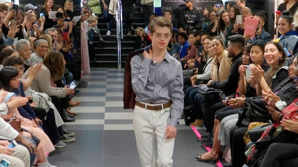 """This image from video taken on Wednesday, Oct. 16, 2019 shows a boy participating in the 2nd annual """"Gigi's Playhouse Fashion Show"""" in New York. (AP Photo/Gary Gerard Hamilton)"""
