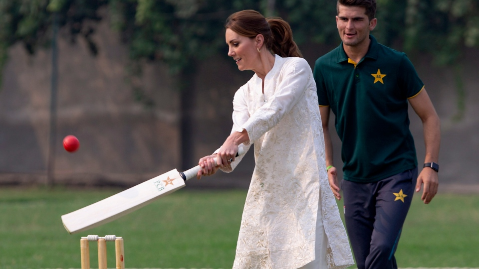 Britain's Kate, Duchess of Cambridge plays cricket as Pakistani bowler Shaheen Afridi looks on, during her visit at the Pakistan Cricket Academy in Lahore, Pakistan, Thursday, Oct. 17, 2019. (AP Photo/B.K. Bangash)