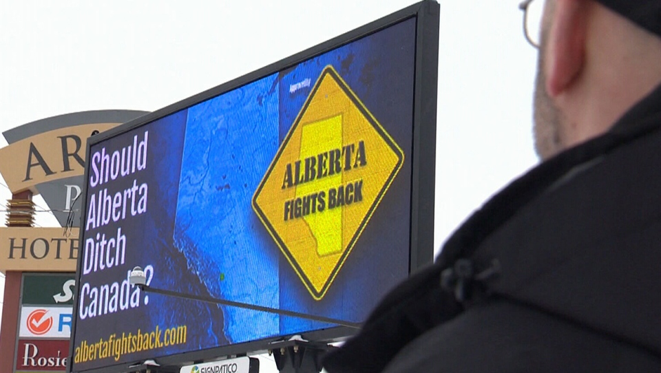 Feb. 2019 image of Peter Downing of Alberta Fights Back standing next to a pro-Alberta separatism billboard in Edmonton