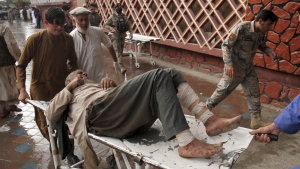 A wounded man is brought by stretcher into a hospital after a mortar was fired by insurgents in Haskamena district of Jalalabad east of Kabul, Afghanistan, on Oct. 18, 2019. (Wali Sabawoon / AP)