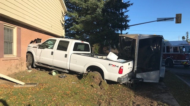Pickup truck hits side of house after two-vehicle crash