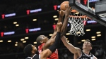 Toronto Raptors forward Serge Ibaka (9) attempts a basket as Brooklyn Nets guard Garrett Temple (17) and forward Rodions Kurucs (00) defend during the second quarter of a preseason NBA basketball game Friday, Oct. 18, 2019, in New York. (AP Photo/Sarah Stier)