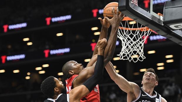 Toronto Raptors forward Serge Ibaka (9) attempts a basket as Brooklyn Nets guard Garrett Temple (17) and forward Rodions Kurucs (00) defend during the second quarter of a preseason NBA basketball game Friday, Oct. 18, 2019, in New York. (AP Photo/Sarah Stier)