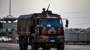Turkish soldiers on a truck drive back from Syria, in the border town of Akcakale, Sanliurfa province, southeastern Turkey, Friday, Oct. 18, 2019. (AP Photo/Emrah Gurel)