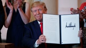 U.S. President Donald Trump holds up an executive order during a signing ceremony that calls for upfront disclosure by hospitals of actual prices for common tests and procedures to keep costs down, at the White House in Washington, Monday, June 24, 2019. (AP Photo/Carolyn Kaster)