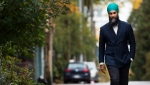 NDP leader Jagmeet Singh walks as a cat crosses by during a campaign stop in Vancouver, B.C., on Saturday, October 19, 2019. THE CANADIAN PRESS/Nathan Denette