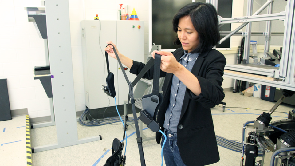 Ornwipa Thamsuwan, a researcher who analyzed farmers' movement, holds an exoskeleton at the University of Saskatchewan. (Courtesy: Chris Morin/USask)