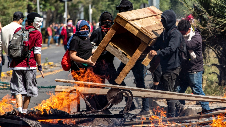 Demonstrators build a burning barricade during a protest in Santiago, Chile, Saturday, Oct. 19, 2019. (AP Photo/Esteban Felix)