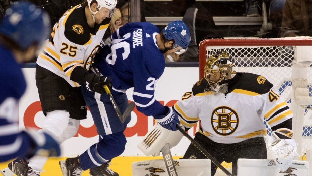 Boston Bruins goaltender Jaroslav Halak (41) keeps his eye on the action as teammate Brandon Carlo (25) takes Toronto Maple Leafs centre Nicholas Shore (26) off the puck during first period NHL hockey action in Toronto, Saturday, Oct. 19, 2019. THE CANADIAN PRESS/Fred Thornhill