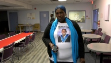 Mary Malueth wears a portrait of her son on a T-shirt to an emergency meeting to address a series of youth deaths within the South Sudanese community. Her 23-year-old son was shot and killed in 2016.