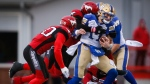 Winnipeg Blue Bombers quarterback Chris Streveler, centre, is swarmed by Calgary Stampeders' players during first half CFL football action in Calgary, Saturday, Oct. 19, 2019. (THE CANADIAN PRESS/Jeff McIntosh)