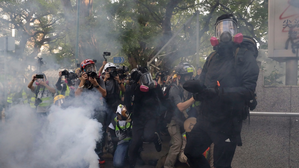 Protesters throw fire bombs amid journalists outside a police station in Hong Kong, Sunday, Oct. 20, 2019. Hong Kong protesters again flooded streets on Sunday, ignoring a police ban on the rally and setting up barricades amid tear gas and firebombs.(AP Photo//Mark Schiefelbein)