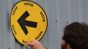 Elections Canada information officer Steven Moyer tapes a voting direction arrow sign to the Fire Hall in the village of Kerwood, Ont., Monday, Oct. 19, 2015. THE CANADIAN PRESS/Dave Chidley