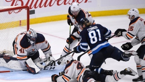 Winnipeg Jets' Kyle Connor (81) looks for the rebound as Edmonton Oilers' Kris Russell (4), Oscar Klefbom (77) and Josh Archibald (15) help Mike Smith (41) during third period NHL action in Winnipeg on Sunday, Oct. 20, 2019. (THE CANADIAN PRESS/Fred Greenslade)