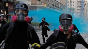 Police use blue dyed water on protestors in Hong Kong, Sunday, Oct. 20, 2019. (AP Photo/Kin Cheung)