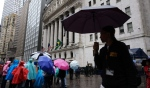 People carry umbrellas as they pass the New York Stock Exchange in New York, on May 13, 2019. (Mark Lennihan / AP)