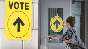 A woman enters a voting station to cast her vote in the 2015 Canadian federal election. (Peter Power/The Canadian Press)