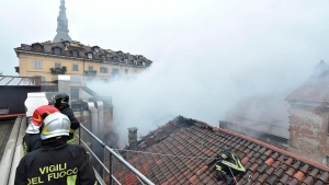 Firefighters work to put out a fire on the rooftop of the Cavallerizza Reale, in Turin, northern Italy, Monday, Oct. 21, 2019. (Alessandro Di Marco/ANSA via AP)