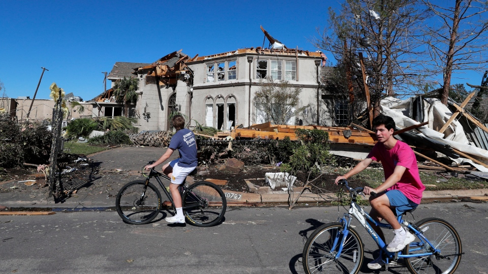 Bicyclists ride past a house damaged by a tornado in the Preston Hollow section of Dallas, Monday, Oct. 21, 2019. (AP Photo/LM Otero)