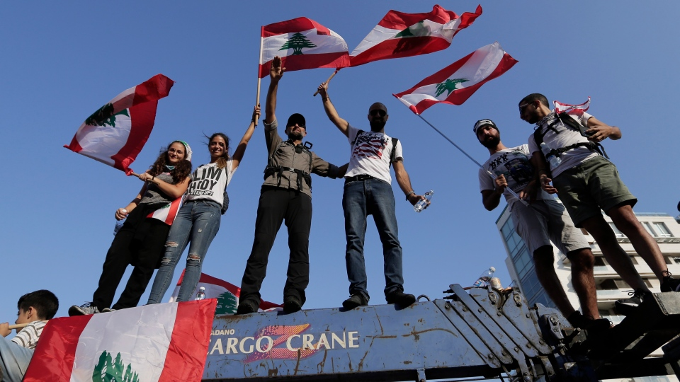 Anti-government protesters shout slogans against the Lebanese government during a protest in Beirut, Lebanon, Monday, Oct. 21, 2019. (AP Photo/Hassan Ammar)