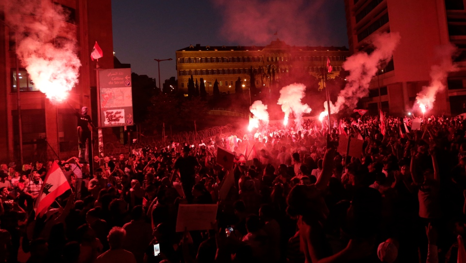 Anti-government protesters light flares and shout slogans against the Lebanese government during a protest in Beirut, Lebanon, Monday, Oct. 21, 2019. (AP Photo/Hassan Ammar)