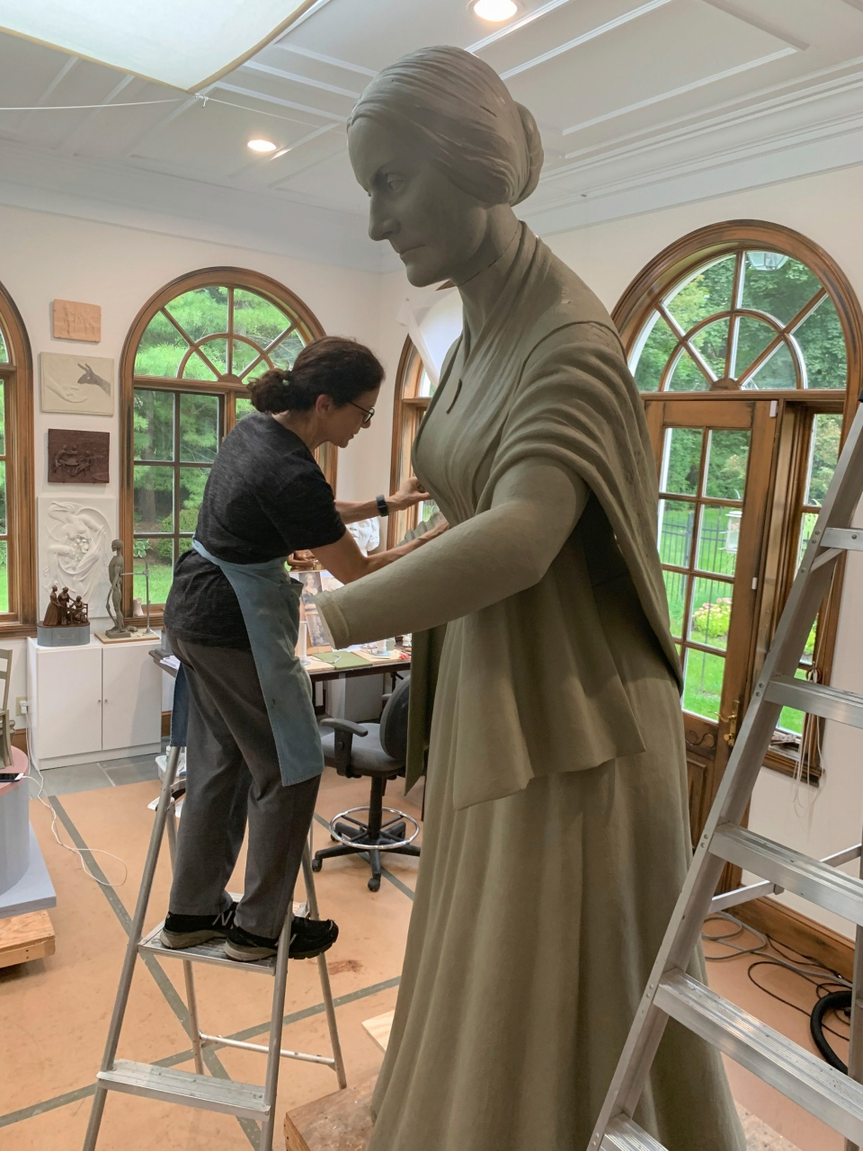 In this Sept. 10, 2019 photo provide by Michael Bergmann, artist Meredith Bergmann works on a sculpture of Susan B. Anthony at her studio in Ridgefield, Conn. (Michael Bergmann via AP)