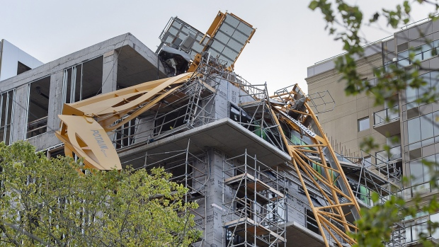 A toppled building crane is draped over a new construction project in Halifax on Sunday, Sept. 8, 2019. A proposed class action lawsuit is looking to recover losses sustained by businesses and residential tenants displaced by the collapse of a construction crane in downtown Halifax last month during post tropical storm Dorian. THE CANADIAN PRESS/Andrew Vaughan