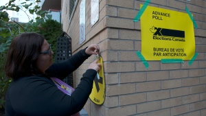 Election worker Shadoe Ball tapes a sign pointing towards an advance voting poll station in the electoral district of Toronto Centre at Muriel Collins Housing Cooperative in Toronto on Friday Oct. 11, 2019. (THE CANADIAN PRESS/Doug Ives)