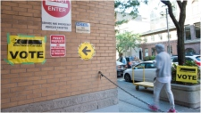 Signs point towards an advance voting poll location at the electoral district of Toronto Centre at Muriel Collins Housing Cooperative in Toronto on Friday Oct. 11, 2019. THE CANADIAN PRESS/Doug Ives