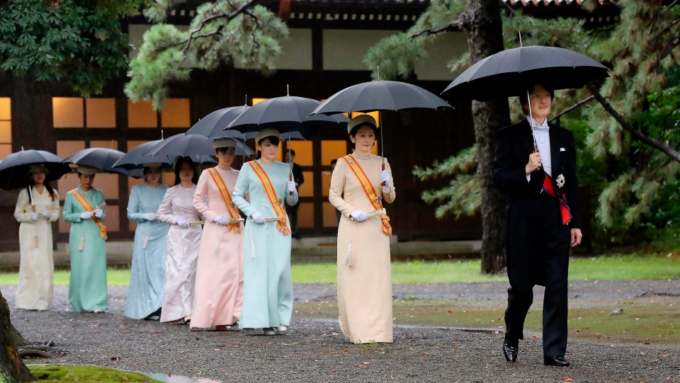 "Japan's Crown Prince Akishino, right, and Crown Princess Kiko, second from right, arrive for the ceremony at ""Kashikodokoro"", one of three shrines at the Imperial Palace, in Tokyo, Tuesday, Oct. 22, 2019. (Kyodo News via AP)"