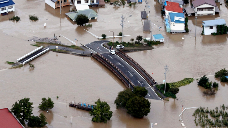 In this Sunday, Oct. 13, 2019, file photo, cars are stranded on a road as the city is submerged in muddy waters after an embankment of the Chikuma River broke, in Nagano, central Japan, following a powerful typhoon. (Yohei Kanasashi/Kyodo News via AP, File)