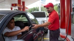 In this Oct. 8, 2019 photo, gas station attendant Leowaldo Sanchez takes a cigarette as payment from a motorist as he fills the tank in San Antonio de los Altos on the outskirts of Caracas, Venezuela. (AP Photo/Ariana Cubillos)