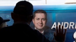 In this Oct. 16, 2019, file photo, a supporter leans on a window as Conservative leader Andrew Scheer's bus arrives at a campaign stop in Hamilton, Ontario. (Adrian Wyld/THE CANADIAN PRESS)