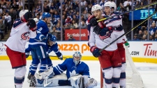 Columbus Blue Jackets centre Alexander Wennberg (10) is congratulated by teammates Zach Werenski (8) and Gustav Nyquist (left) after scoring the game-tying goal on Toronto Maple Leafs goaltender Frederik Andersen (31) during third period NHL action in Toronto on Monday, October 21, 2019. Leafs Justin Holl (3) and Trevor Moore (42) react with Andersen. (THE CANADIAN PRESS/Frank Gunn)