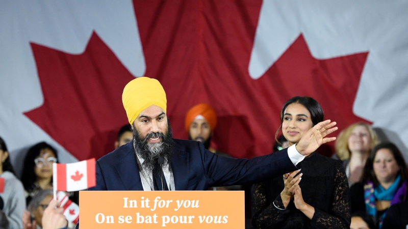 NDP leader Jagmeet Singh addresses supporters as his wife Gurkiran Kaur looks on at NDP election headquarters in Burnaby, B.C. on Monday, Oct. 21, 2019. THE CANADIAN PRESS/Nathan Denette