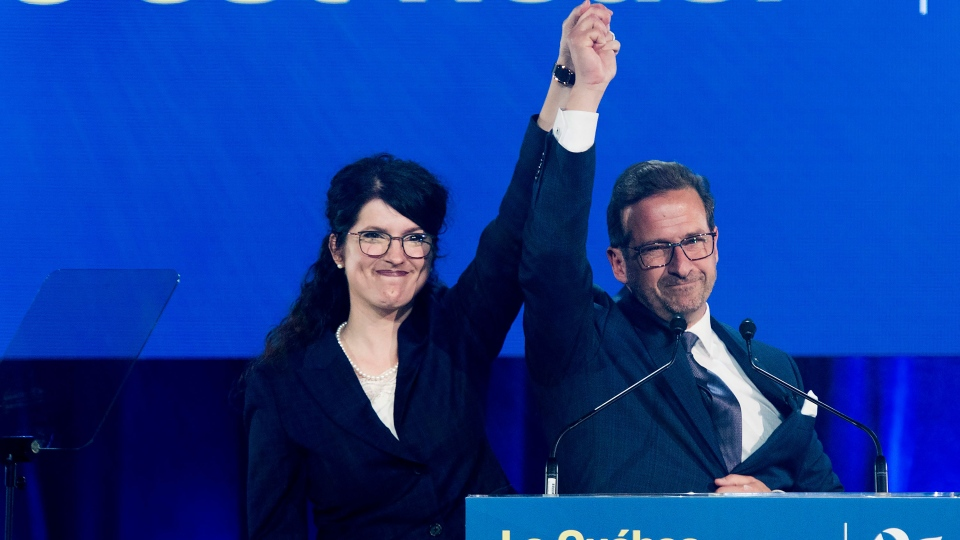 Bloc Quebecois leader Yves-Francois Blanchet has his hand raised by wife Nancy Deziel as he speaks to supporters on federal election night in Montreal, early Tueday morning, October 22, 2019. THE CANADIAN PRESS/Graham Hughes