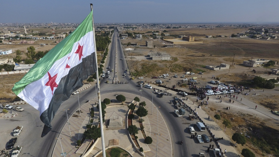 Syria's opposition flag flies on a pole in Tal Abyad, Syria, on Oct. 22, 2019. (Fatih Isci / Turkish Red Crescent via AP)